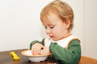 Adorable kid boy eating soup with his hands