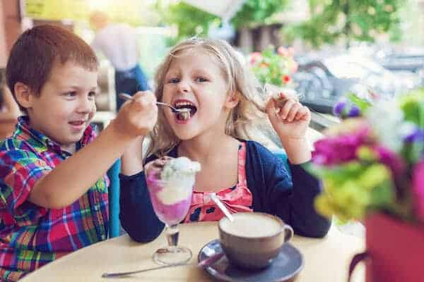 Little bro and sis eating ice cream at an outdoor cafe in outdoor cafe