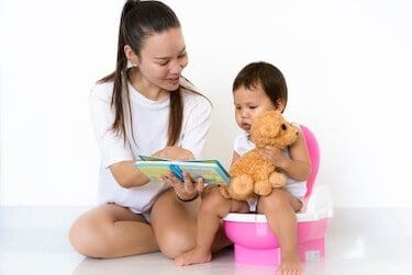 Mother teaching child to potty train while reading a book