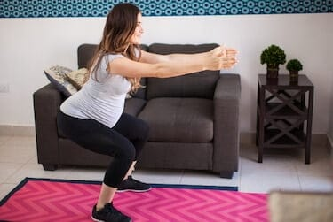 Full length view of a young pregnant mother exercising and doing squats at home