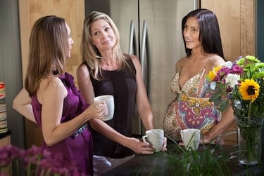 Two pregnant women hold mugs mugs with a friend in the kitchen