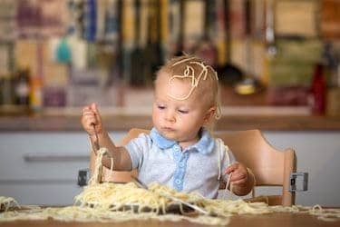 Little baby eating spaghetti for lunch and making a mess at home in kitchen