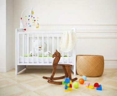 Empty nursery room with basket, toys and wooden horse