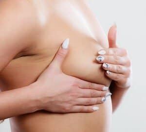 Young woman examining her breasts for lumps or signs of breast cancer