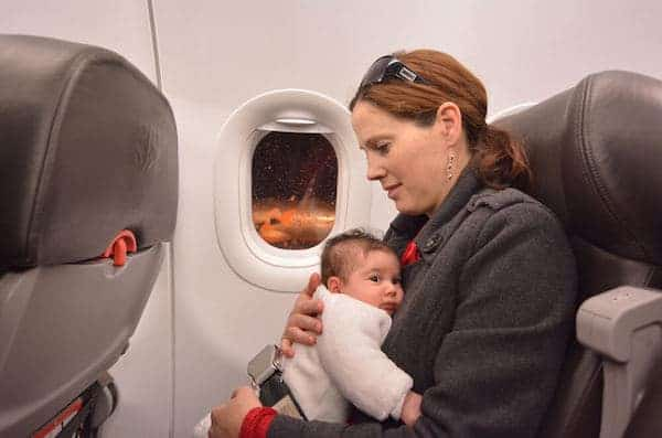 Mother holding her newborn inside of a flight