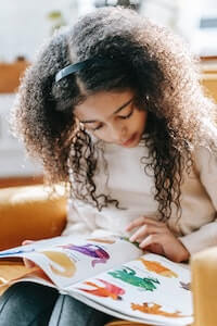 Child studying colorful pictures in book