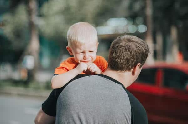 father carries crying child