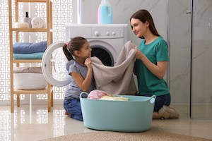 kid helping mom in laundry