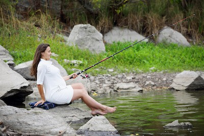 pregnant woman fishing on the river bank