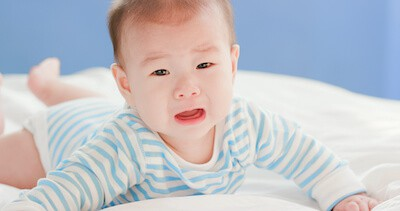 baby lying on bed and cry